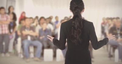 photo d'une femme prise de dos, face à un auditoire flouté