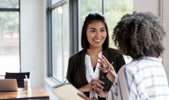 Photos de deux femmes qui discutent à un bureau