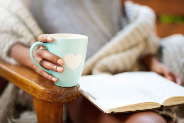 Femme qui lit un livre avec un thé dans les mains.
