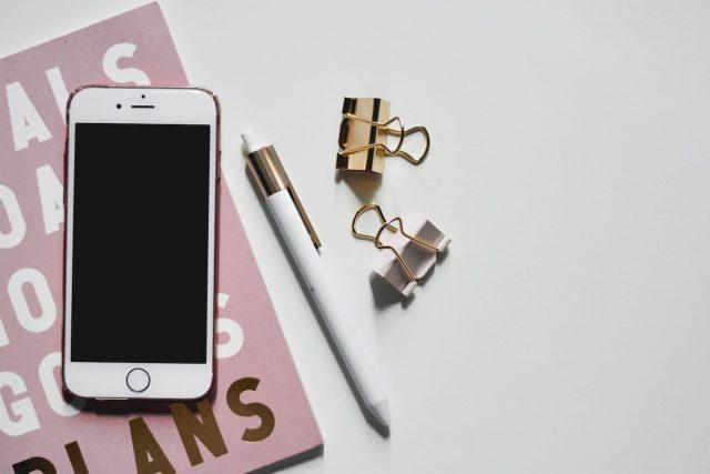 Photo d'un journal, un téléphone, un crayon et des pinces de bureau