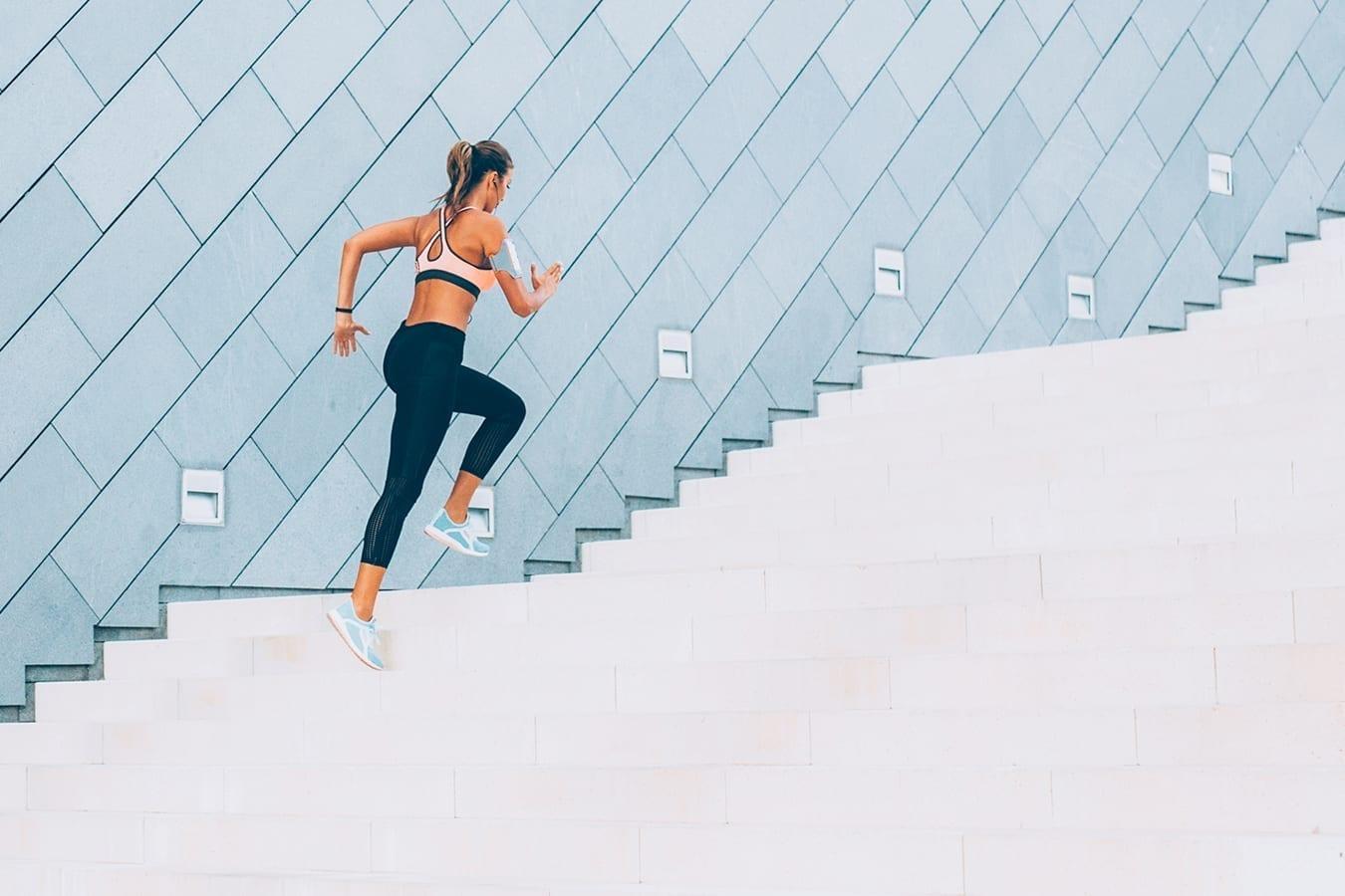 Femme sportive qui monte des escaliers.