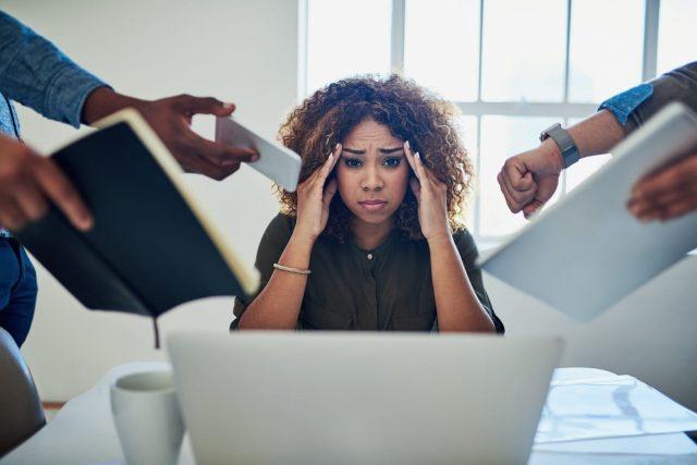 Photo d'une femme se tenant la tête, entourée de dossiers tendues vers elle au travail