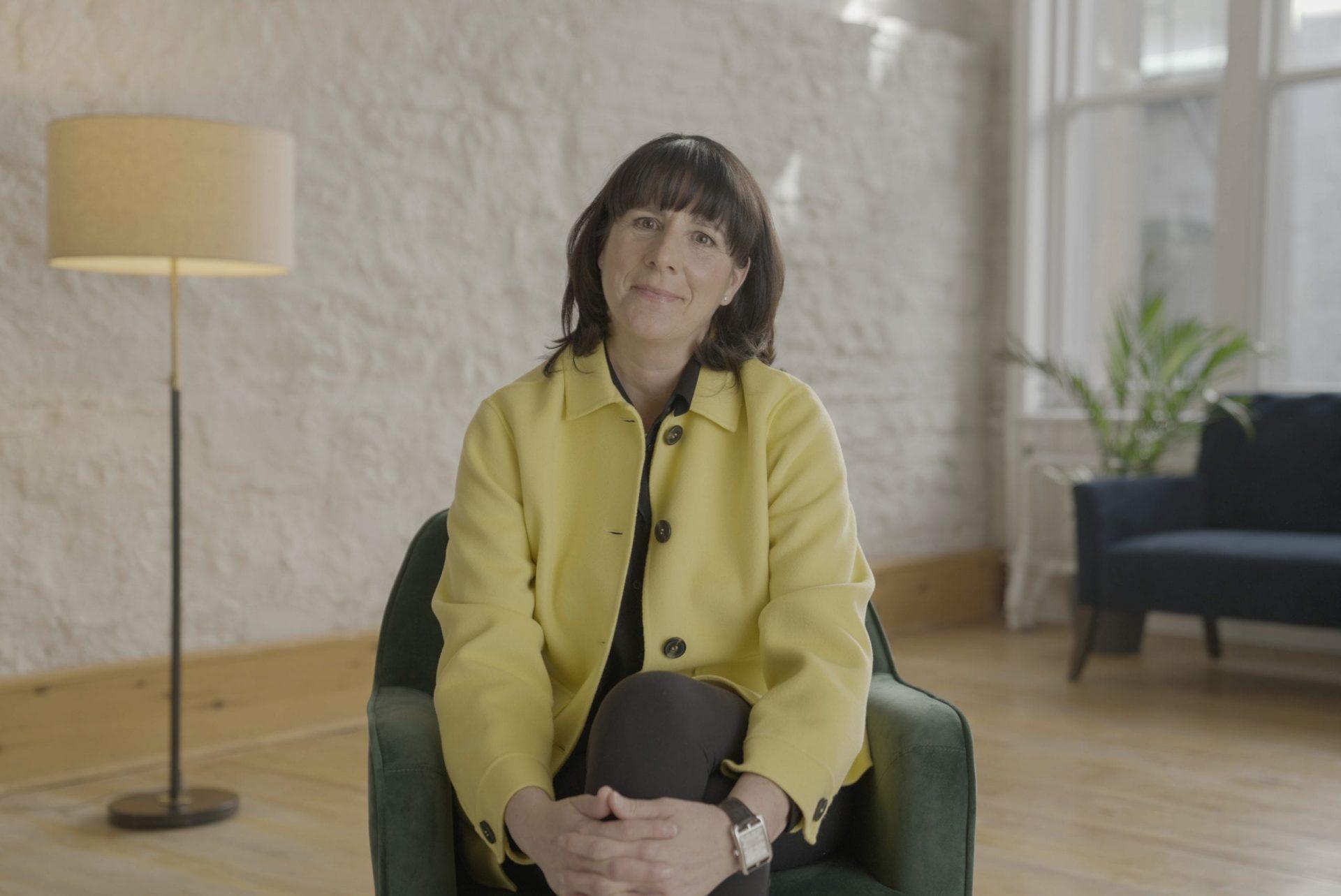 Sophie Brochu assise sur un fauteuil vert sourire au visage et bras croisés sur les genoux.