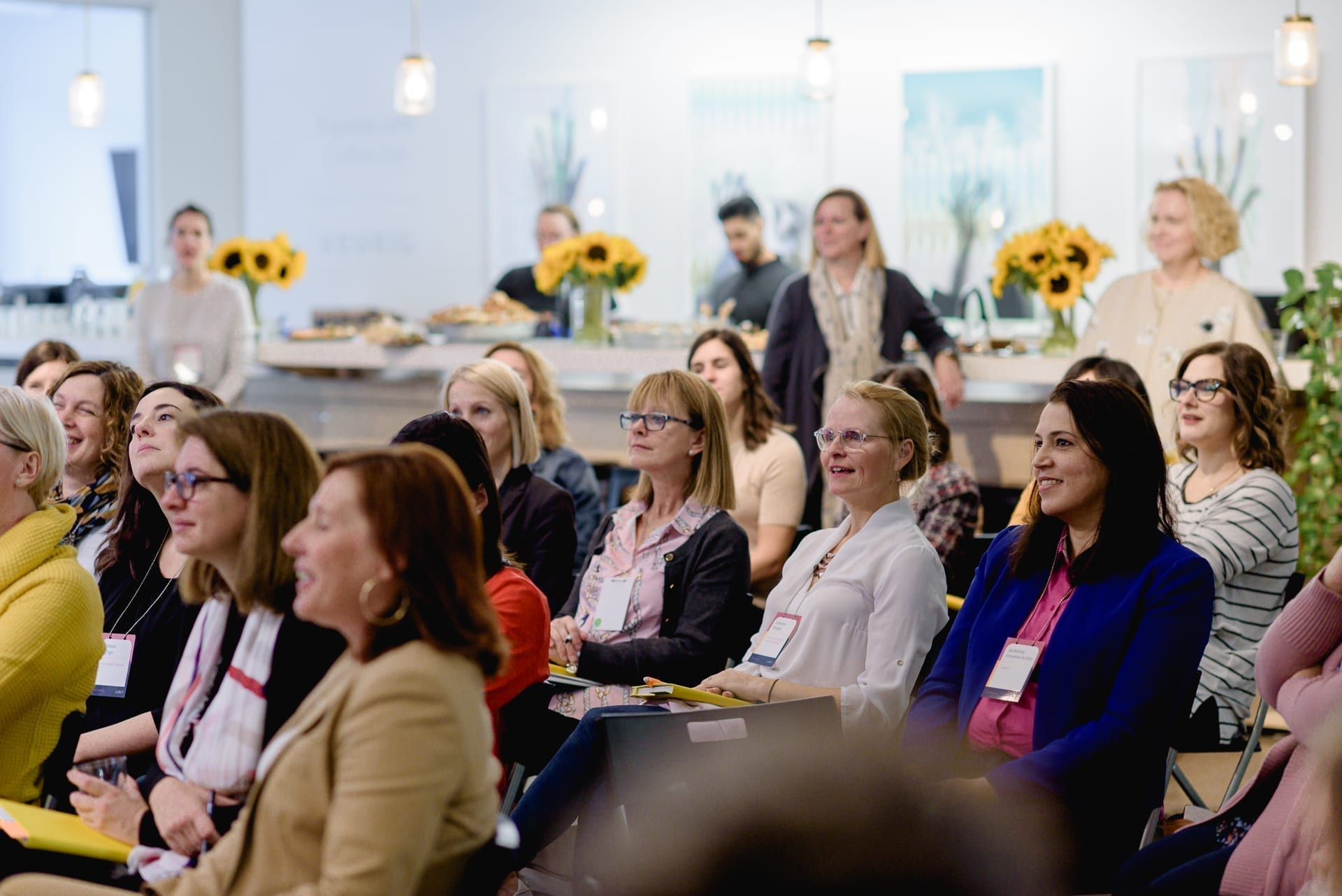 Femmes assises avec blocs notes à la main et écoutant l'orateur lors d'un évènement L'effet A.