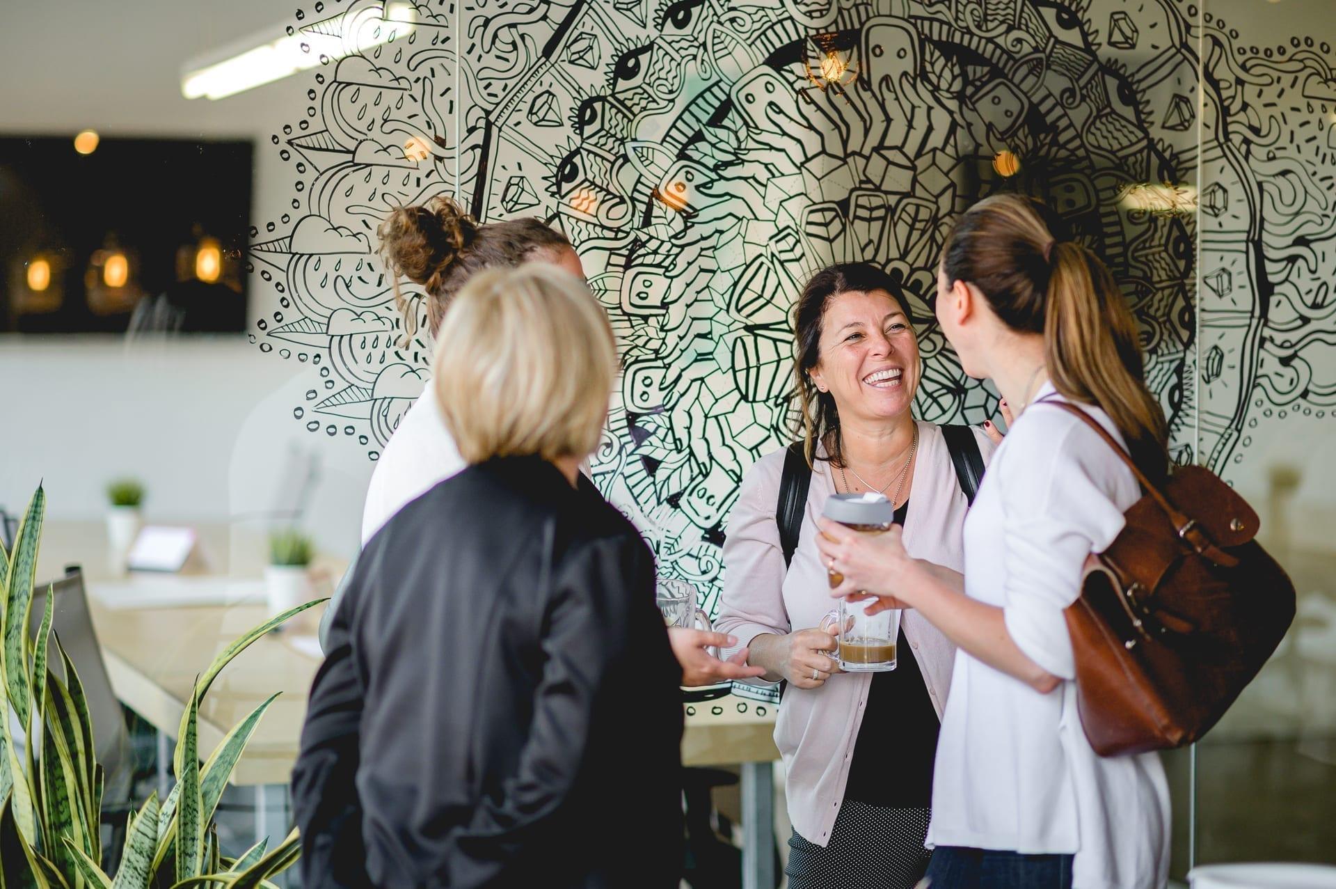 Plusieurs femmes en petit groupe discutent autour d'un café debout.