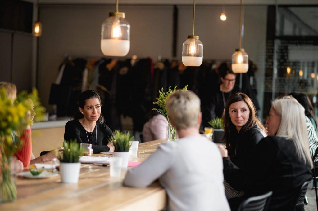 Femmes qui échangent autour d'une table de conférence pendant un événement L'effet A.