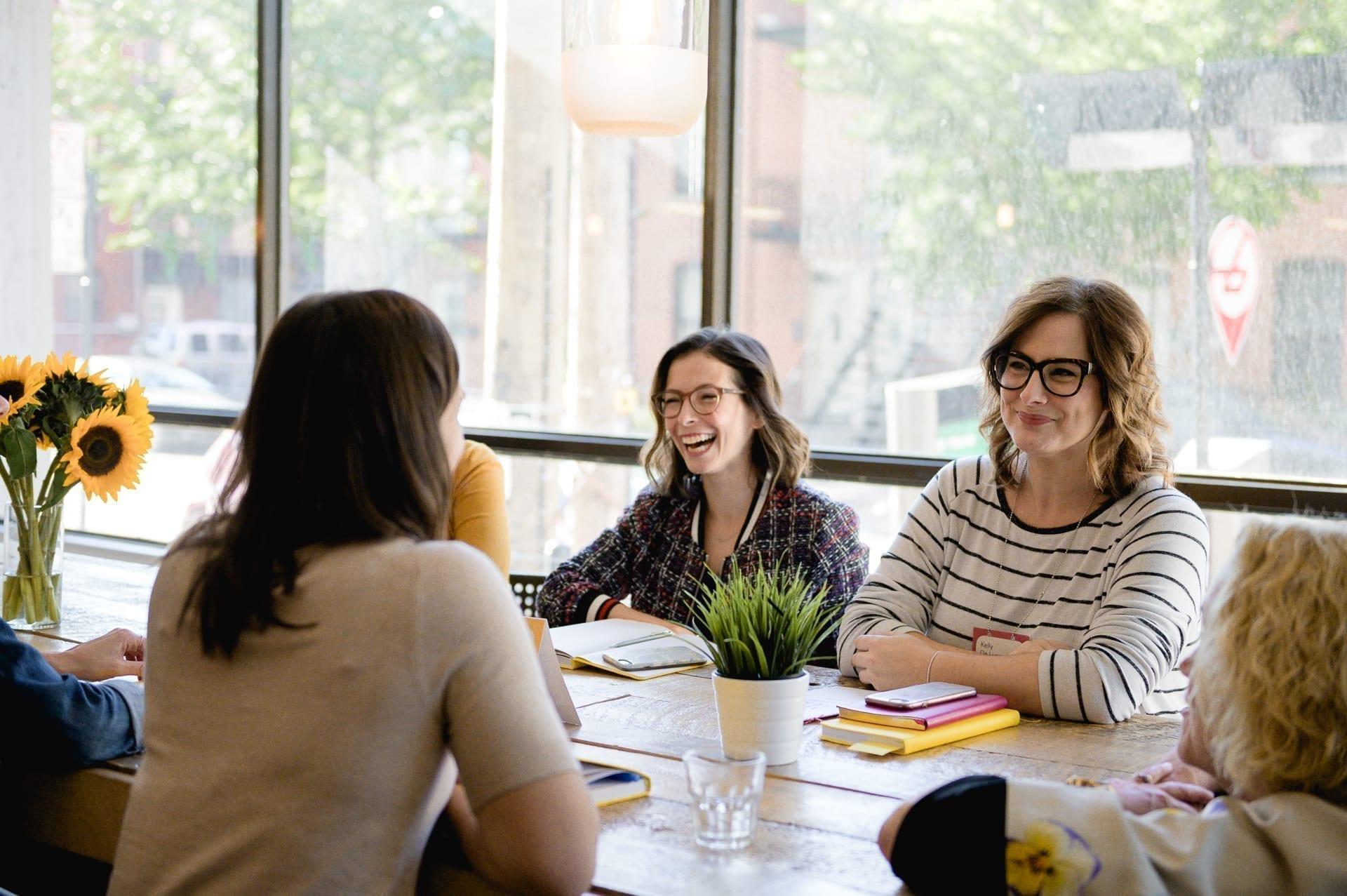 Femmes qui rient autour d'une table de conférence pendant un atelier L'effet A.
