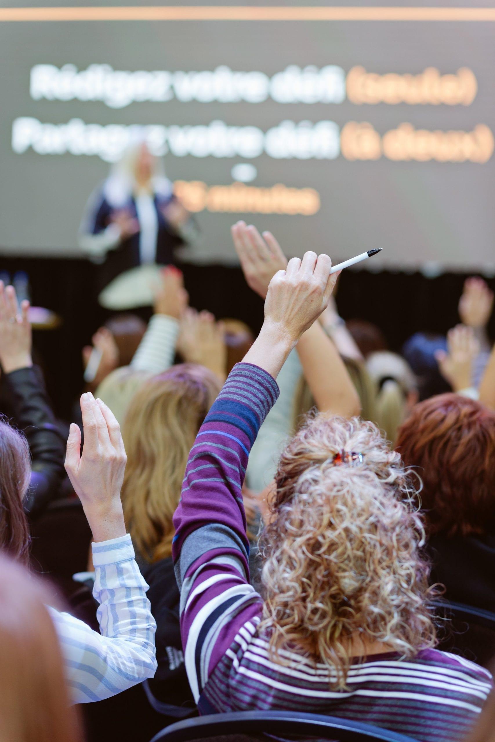 Femmes qui lèvent la main lors d'une conférence aux locaux L'effet A.
