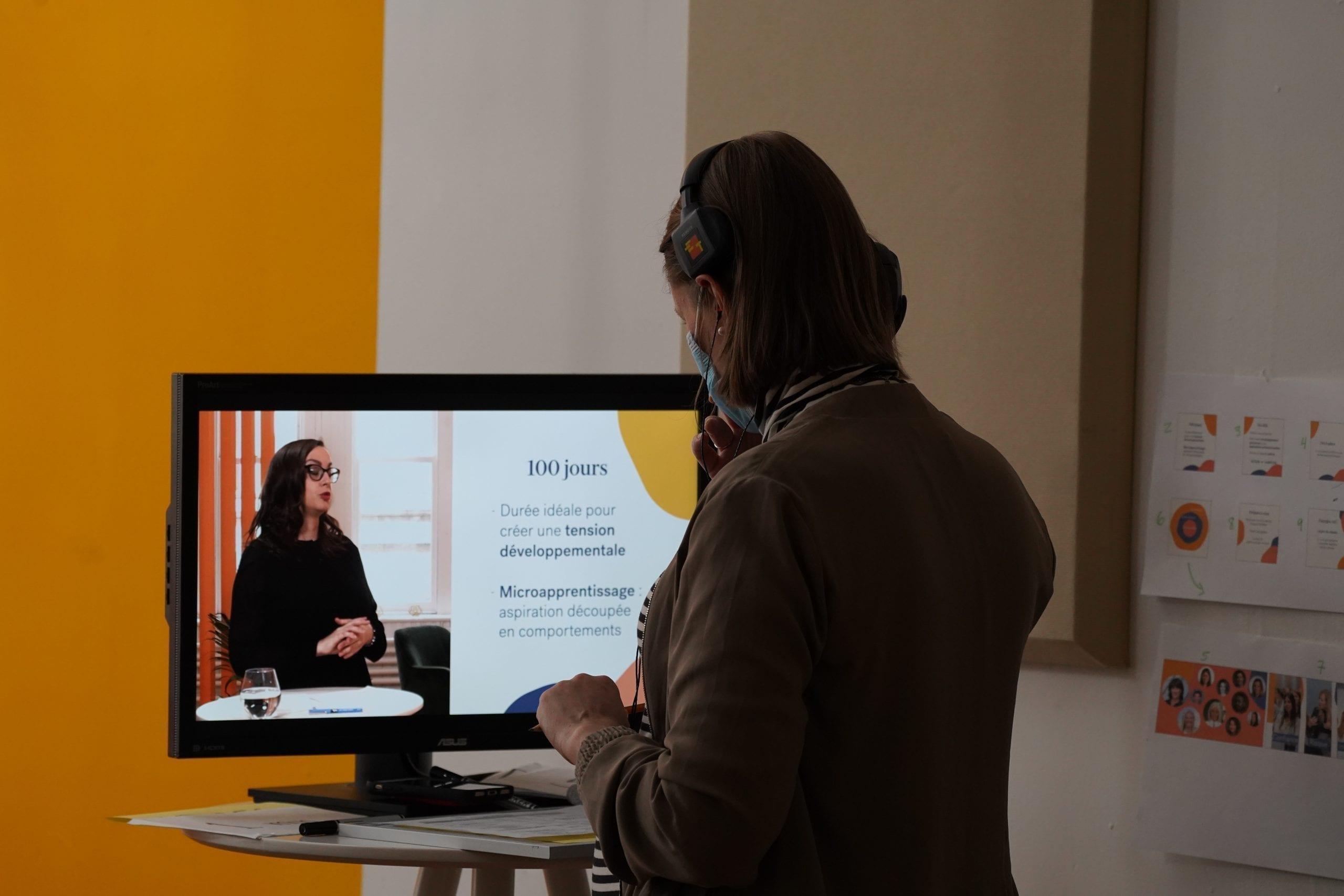 Femme qui regarde un tournage vidéo sur écran.