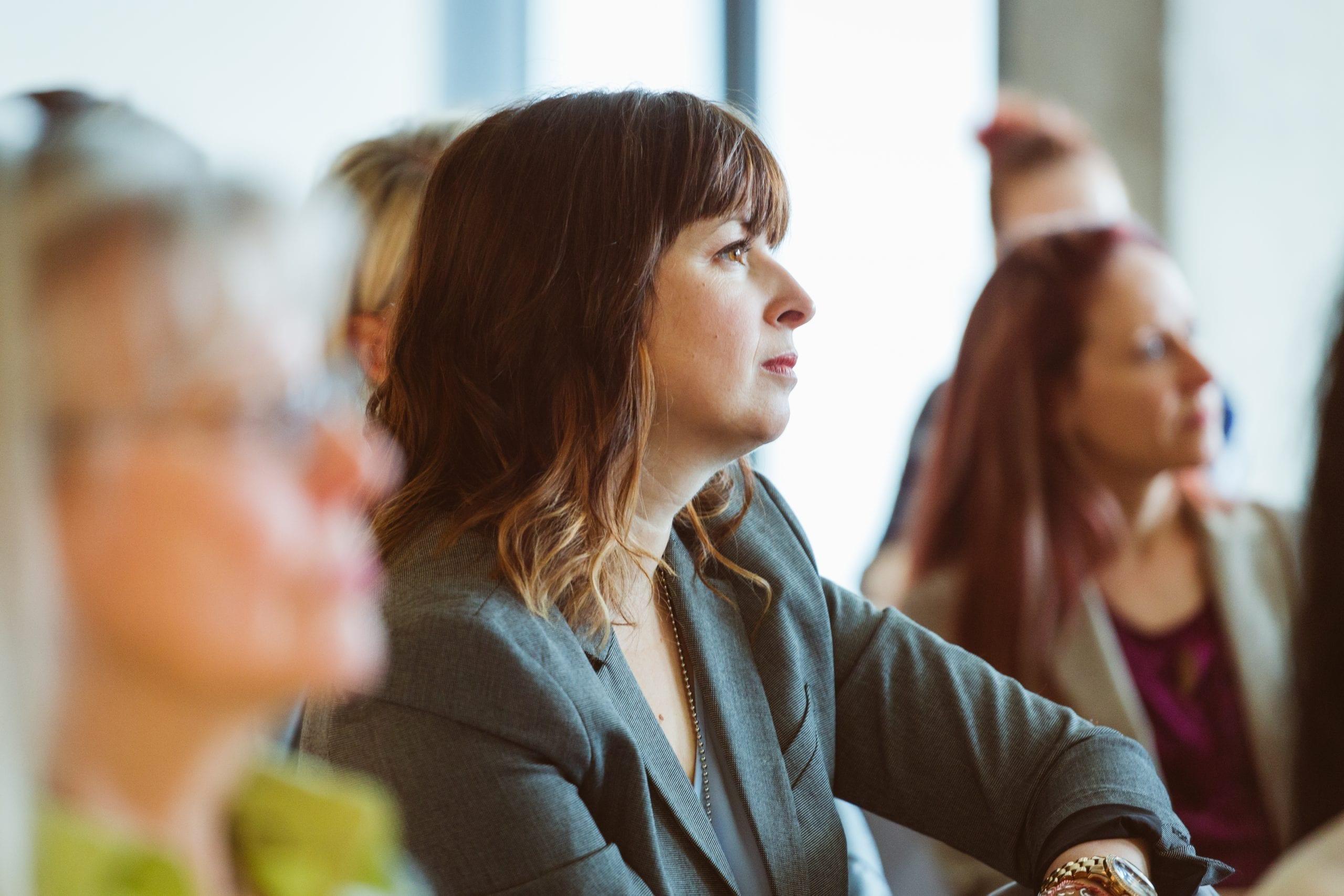 Femme de profil qui est concentrée lors d'une conférence L'effet A.