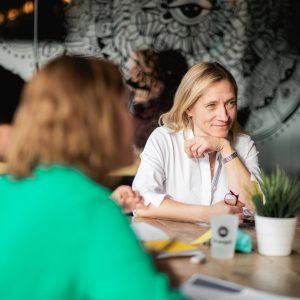 Femme assise à une table, qui regarde avec concentration une autre femme