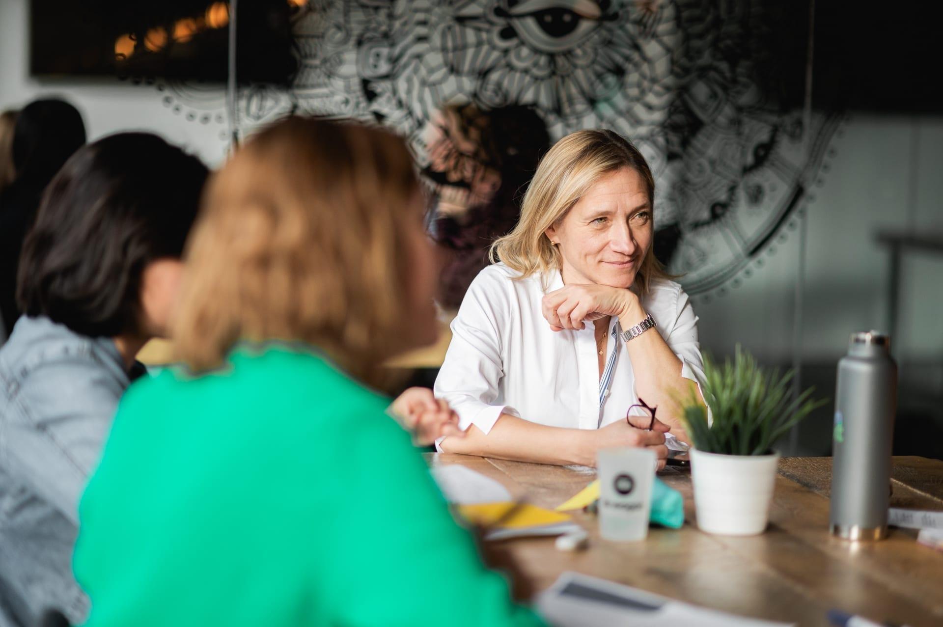Femme au bout d'une table qui regarde quelqu'un d'autre avec concentration