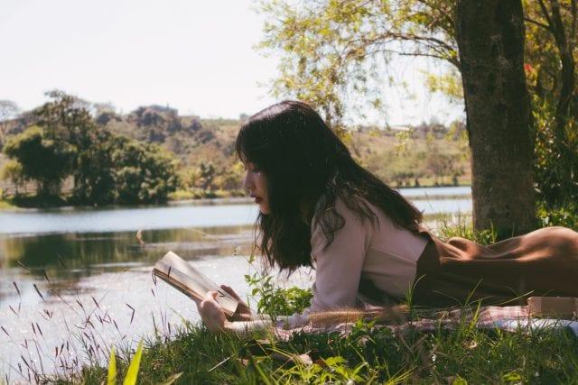 jeunne fille en bord de lac, lisant un livre